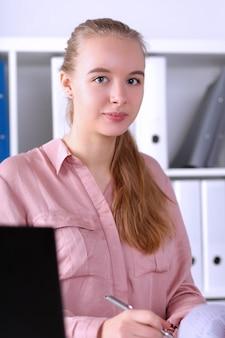 Ritratto di donna d'affari con gioia e calma. businesslady carino seduto sul posto di lavoro. segretario in carica. concetto di business e società