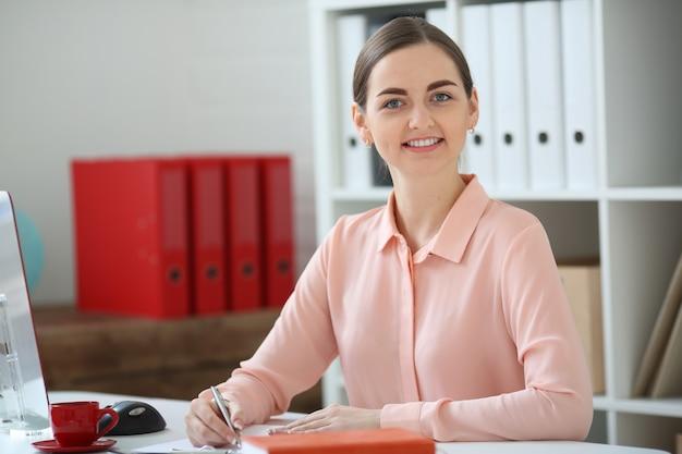 Ritratto di donna d'affari. è seduto in un ufficio al tavolo e guarda la telecamera e tiene in mano una penna