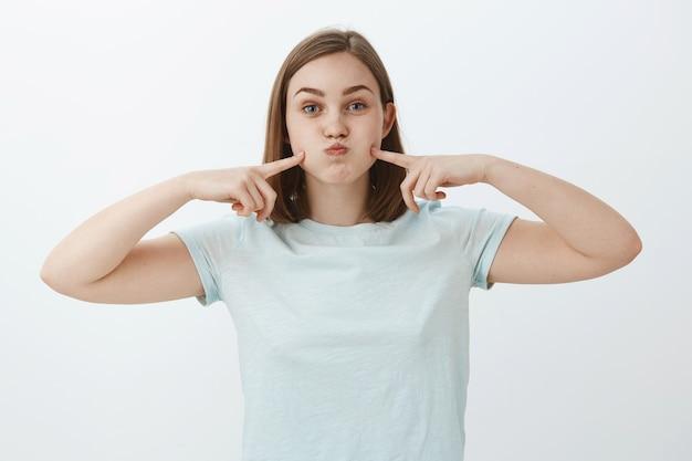 Ritratto di donna europea carina spensierata in maglietta azzurra casual imbronciato, trattenendo il respiro e colpendo le guance con le dita indice divertendosi a passare il tempo sul muro grigio cercando di divertirsi