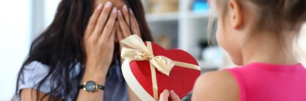 Ritratto di donna felice che copre gli occhi a mano e in attesa di sorpresa dal bambino. piccola figlia che tiene giftbox a forma di cuore festivo.