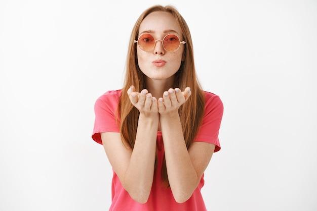 Ritratto di donna femminile spensierata e sicura alla moda in occhiali da sole rotondi rosa che soffia bacio amorevole caldo