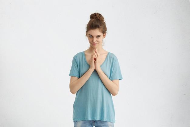 Ritratto di donna furba guardando con occhi astuti tenendo le mani insieme cercando di chiedere qualcosa in modo sornione.