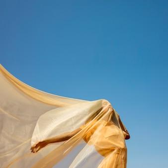 Ritratto di donna gioiosa con un panno giallo in natura