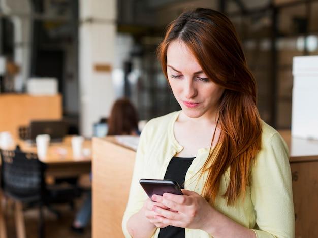Ritratto di donna giovane attraente utilizzando smartphone