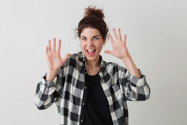 Ritratto di donna giovane bella hipster, alzando le mani, pazza espressione divertente del viso, emotivo, felice, ridendo, positivo, divertirsi, isolato, camicia a scacchi