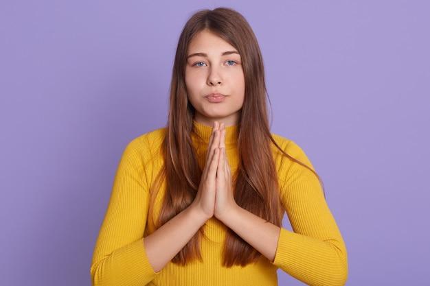 Ritratto di donna graziosa con bei capelli lunghi in camicia gialla casual tenendo insieme le palme e pregando
