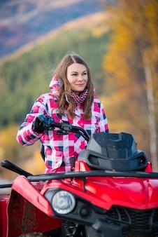 Ritratto di donna graziosa in abbigliamento invernale su quad bike rossa guardando in lontananza