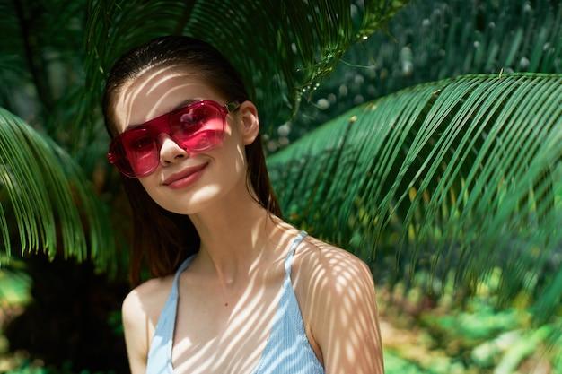 Ritratto di donna in bicchieri, foglie verdi di palme, bel viso