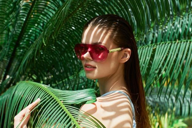 Ritratto di donna in bicchieri su una delle foglie verdi di palme, bel viso