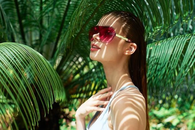 Ritratto di donna in bicchieri su uno sfondo di foglie verdi di palme, bel viso