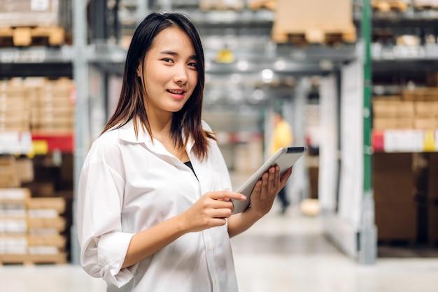 Ritratto di donna lavoratore manager in piedi e dettagli dell'ordine su computer tablet per forniture che guarda l'obbiettivo sugli scaffali con sfondo di merci in magazzino