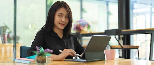 Ritratto di donna libero professionista che lavora con tavoletta digitale sul tavolo da lavoro