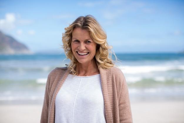 Ritratto di donna matura in piedi sulla spiaggia