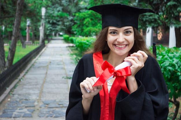 Ritratto di donna nel suo giorno di laurea. università. istruzione, laurea e concetto di persone