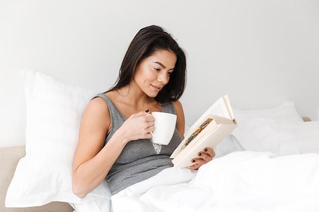 Ritratto di donna pacifica compiaciuta con lunghi capelli castani che riposa nel letto comodo dopo il sonno, con libro di lettura e bere caffè