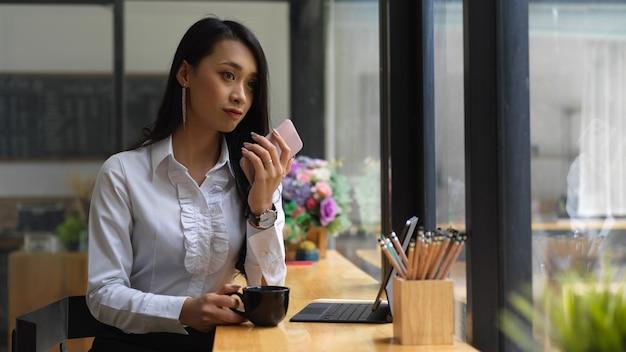 Ritratto di donna riposarsi con una tazza di caffè e guardare attraverso la finestra nella caffetteria