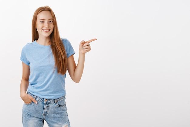 Ritratto di donna rossa carina calma e rilassata dall'aspetto amichevole con le lentiggini tenendo la mano in tasca avendo una conversazione informale e indicando a destra sorridendo gioiosamente