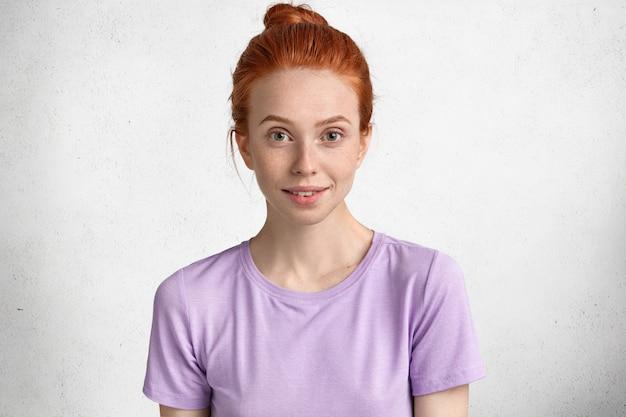 Ritratto di donna rossa dall'aspetto piacevole con nodo di capelli, guarda con gioia alla telecamera, indossa una maglietta viola casual, esprime emozioni positive