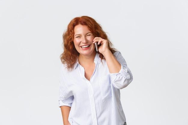Ritratto di donna rossa di mezza età allegra e bella che parla sul telefono, che tiene smartphone e che sembra felice mentre conversa, buoni ricevimenti del cellulare, servizio cellulare.