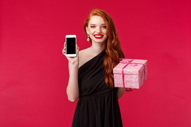 Ritratto di donna rossa elegante e alla moda che mostra il display del telefono cellulare e una confezione regalo rosa, raccomandare il negozio o il servizio di consegna per acquistare regali per la tua ragazza, sorridente, su un muro rosso