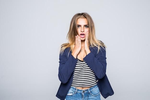 Ritratto di donna scioccata con la bocca aperta che guarda lontano isolato su un muro grigio