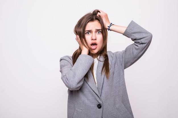 Ritratto di donna scioccata con la bocca aperta guardando lontano su uno sfondo grigio