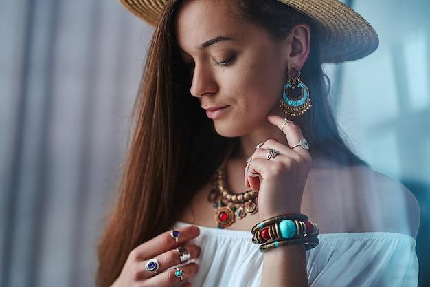 Ritratto di donna sensuale boho chic bruna che indossa camicia bianca e cappello di paglia con orecchini, bracciali, collana e anelli. vestito bohemien zingaro alla moda hippie con dettagli di gioielli