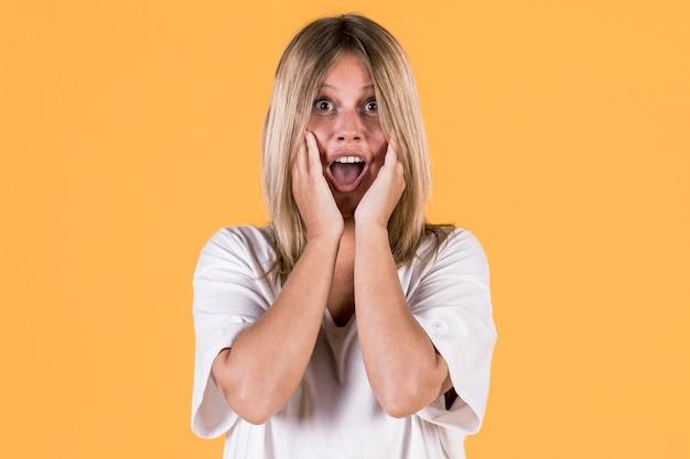 Ritratto di donna sorda sorpresa davanti a sfondo colorato