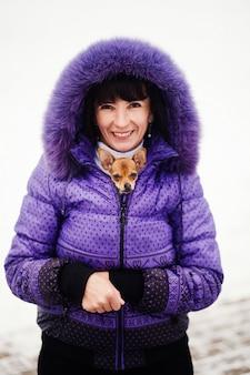Ritratto di donna sorridente con cagnolino tra le braccia