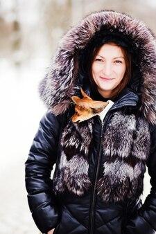 Ritratto di donna sorridente con il giocattolo russo tra le braccia