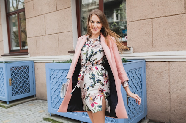 Ritratto di donna sorridente elegante attraente che cammina via della città in cappotto rosa e abito floreale