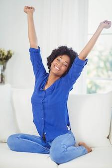 Ritratto di donna sorridente sul divano con le braccia alzate