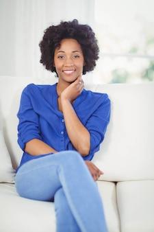 Ritratto di donna sorridente sul divano di casa