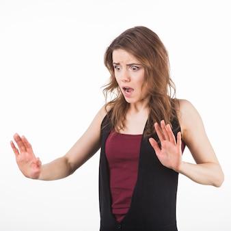 Ritratto di donna spaventata alzando le mani in difesa