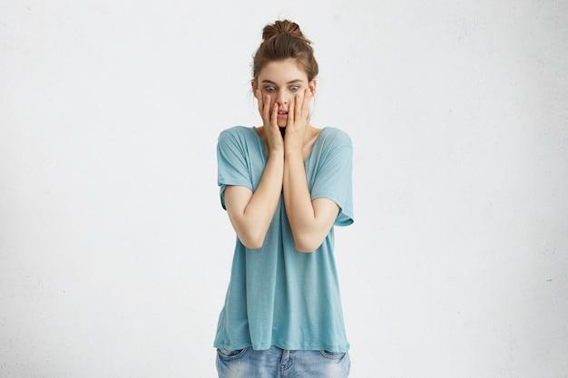 Ritratto di donna stressata che spunta fuori gli occhi e si tiene le mani sul viso, avendo uno sguardo perplesso e frustrato mentre deve parlare di fronte a tutta la classe, avendo paura di parlare in pubblico
