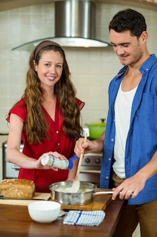 Ritratto di donna versando latte mentre l'uomo mescolando la pastella in padella