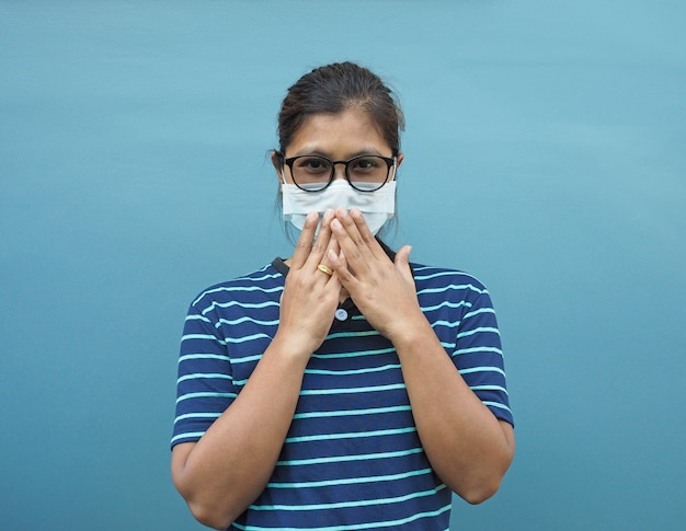 Ritratto di donne asiatiche che indossano occhiali e maschere protettive. mentre si copre la bocca su uno sfondo blu