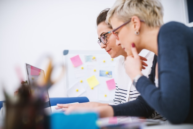 Ritratto di donne di mezza età professionali che lavorano insieme su progetti in ufficio.