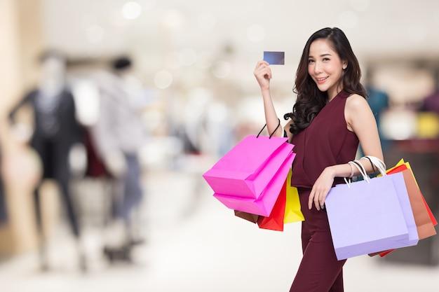 Ritratto di donne felici in vestito rosso che tiene i sacchetti della spesa e carta di credito