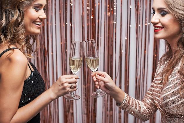 Ritratto di due belle donne eleganti tintinnio di bicchieri di champagne.