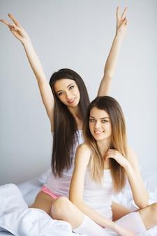 Ritratto di due belle ragazze allegre con un sorriso raggiante huging
