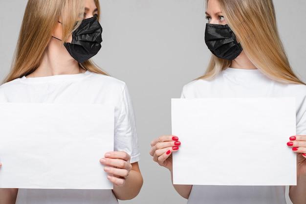 Ritratto di due belle ragazze con lunghi capelli biondi e maschera medica nera sul viso