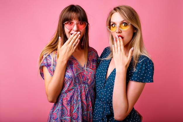 Ritratto di due donne migliori amiche positive che si divertono al muro rosa, indossando abiti estivi vintage stampati luminosi e occhiali da sole, spettegolando insieme, emozioni uscite.