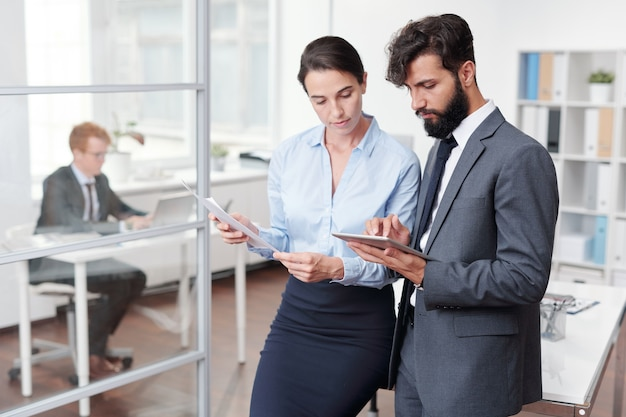 Ritratto di due giovani uomini d'affari, uomo e donna, citando in giudizio tablet insieme mentre si lavora in ufficio, copia dello spazio