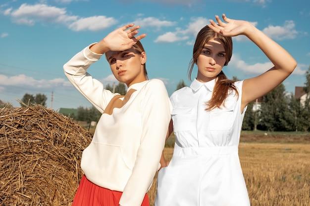 Ritratto di due ragazze bionde in abiti eleganti e alla moda, sullo sfondo di un campo e una pila di paglia