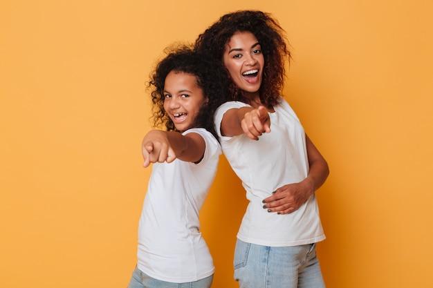 Ritratto di due sorelle africane sorridenti in piedi schiena contro schiena