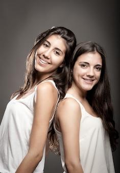 Ritratto di due sorelle schiena contro schiena
