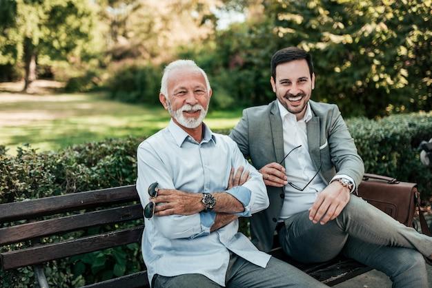 Ritratto di due uomini eleganti seduti su una panchina. guardando la fotocamera