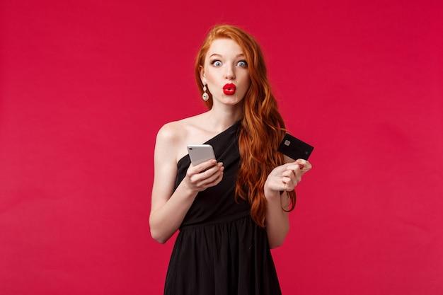 Ritratto di eccitato bella femmina shopaholic in abito elegante nero, con smartphone e carta di credito, labbra piegate stupite, vedi sconto speciale per il compleanno, stand muro rosso