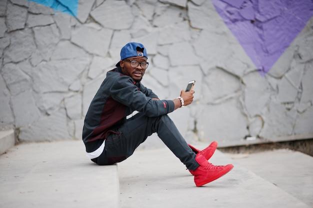 Ritratto di elegante uomo afroamericano su abiti sportivi, cappello e occhiali seduto sulle scale con il telefono a portata di mano. gli uomini neri modellano la moda di strada.